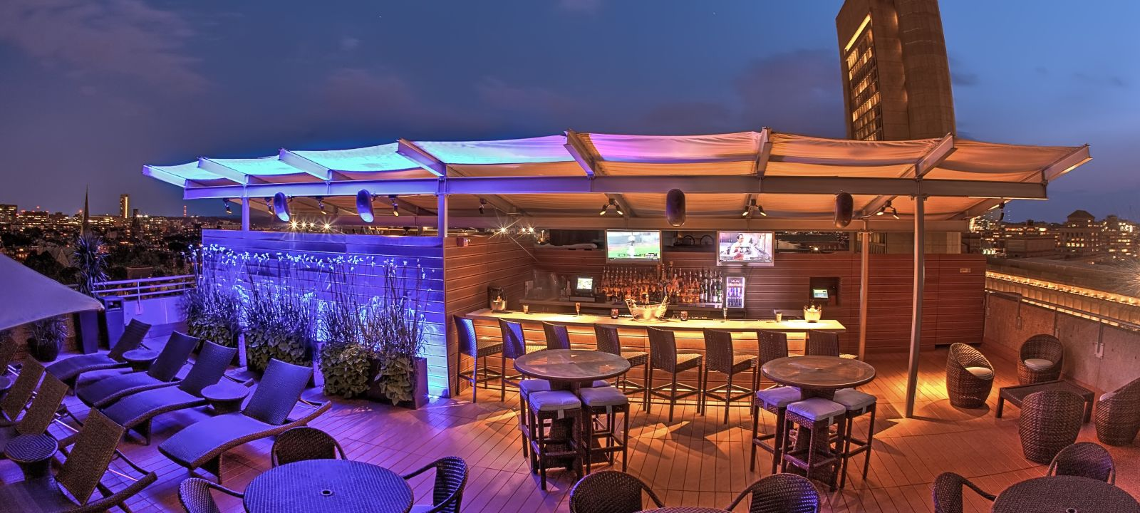 The Colonnade hotel with rooftop bar in Boston along with tables and chairs at night