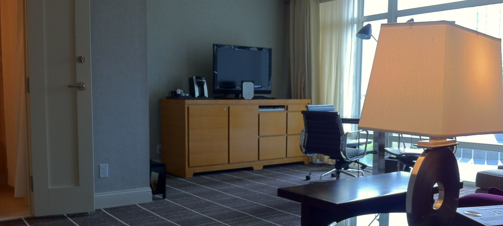 Hotel suite in Boston with separate living room area with a large window and flat screen tv